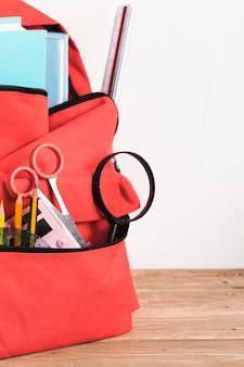 Mochila escolar vermelha com suprimentos essenciais