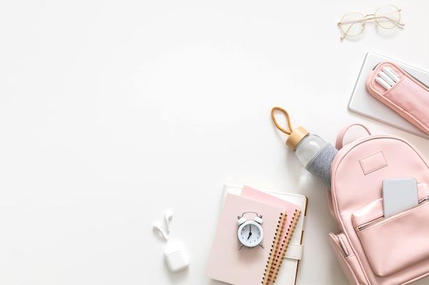 Mochila feminina elegante de vista superior cheia de material de papelaria isolado. conceito de volta às aulas