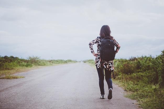 Mochila garota feliz no fundo da estrada e floresta