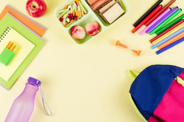 Mochila, lancheira escolar e artigos de papelaria na área de trabalho em tons pastel, espaço de cópia