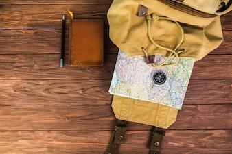 Mochila, mapa e bússola sobre fundo de madeira com diário e caneta