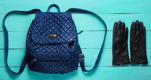 Mochila na moda couro, luvas na superfície de madeira azul. acessórios de tendência.