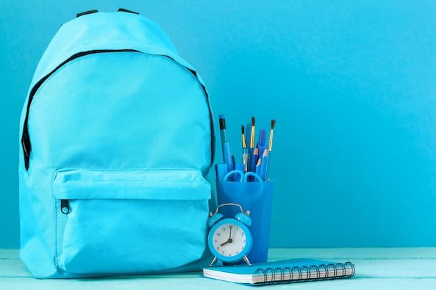 Mochila preparada com material de papelaria escolar e despertador para a volta às aulas.