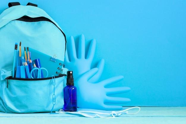 Mochila preparada com material de papelaria escolar e máscara médica, luvas desinfetante de mãos para a volta às aulas.