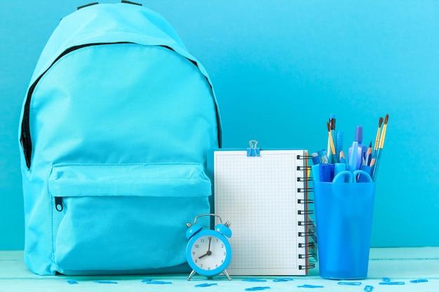 Mochila preparada com material em branco vazio e material de papelaria escolar, despertador para a volta às aulas.