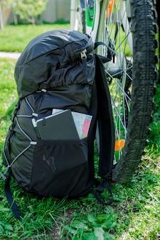 Mochila preta com caderno, mapa e lápis perto de uma bicicleta