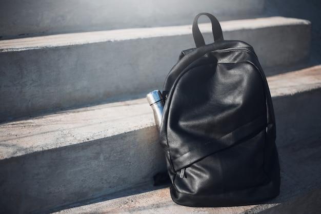 Mochila preta com garrafa térmica de aço reutilizável em escada urbana.