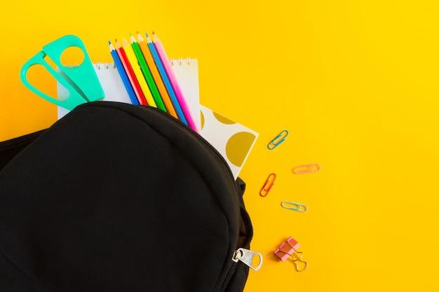 Mochila preta e material escolar sobre um fundo amarelo com espaço de cópia, configuração plana.