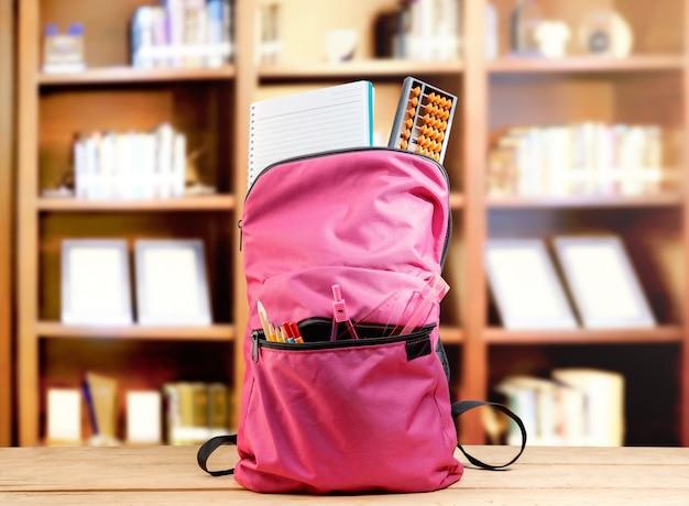 Mochila rosa com livro e diferentes artigos de papelaria na mesa de madeira