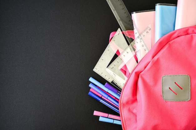 Mochila rosa com material escolar