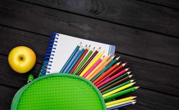 Mochila verde, cheia de material escolar. volta ao conceito de escola