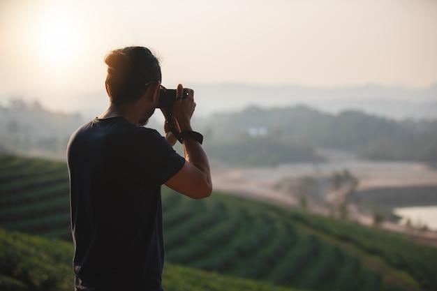 Mochilas de homens asiáticos e viajante caminhando juntos e felizes estão tirando foto na montanha