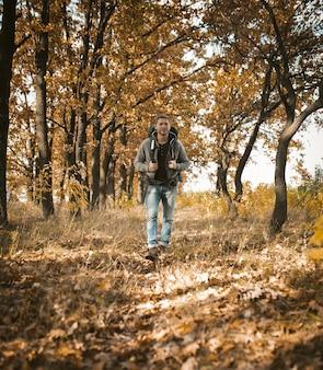 Mochileiro caminha na floresta de outono