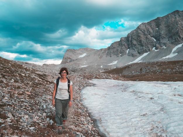Mochileiro da mulher que caminha na paisagem idílico, na cachoeira e no prado de florescência. aventuras de verão e exploração nos alpes. em tons.