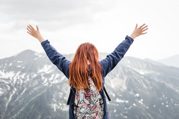 Mochileiro de jovem bem sucedido abre os braços no pico da montanha. menina bonita ruiva fica nas montanhas de neve da primavera. conceito de trekking e turismo. copie o espaço