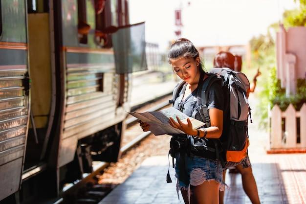 Mochileiro de jovem mulher asiática e viajando olhando o mapa
