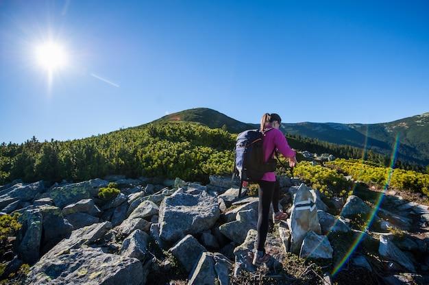 Mochileiro de mulher caminhando na trilha rochosa