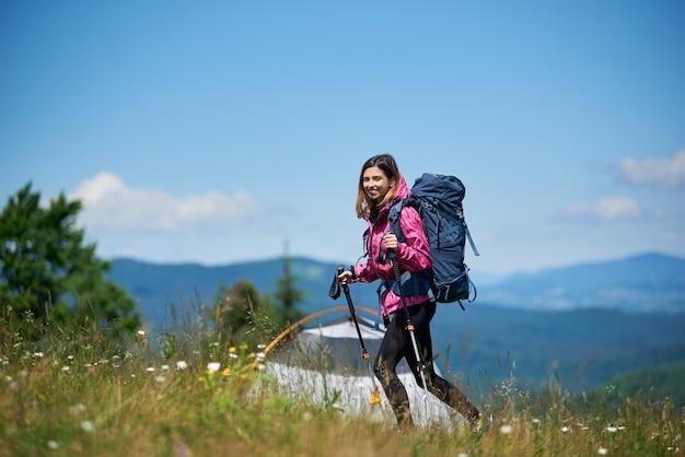 Mochileiro de mulher com mochila e trekking varas perto da tenda, andando no topo de uma colina contra o céu azul, aproveitando o dia ensolarado nas montanhas.