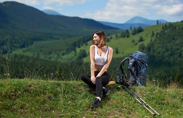 Mochileiro de mulher desportivo com pólos de mochila e trekking, sentado com os olhos fechados, relaxando depois de subir no topo de uma colina, aproveitando o dia ensolarado nas montanhas