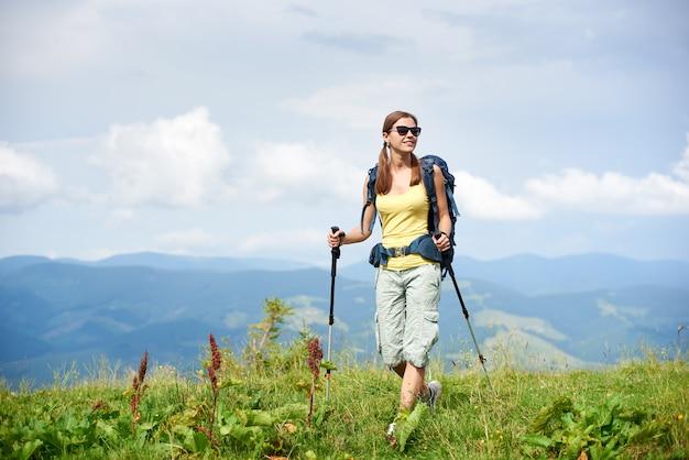 Mochileiro de mulher feliz atleta caminhadas trilha de montanha, andando na colina gramada, usando bengalas, aproveitando o dia nublado de verão. atividade ao ar livre, conceito de turismo