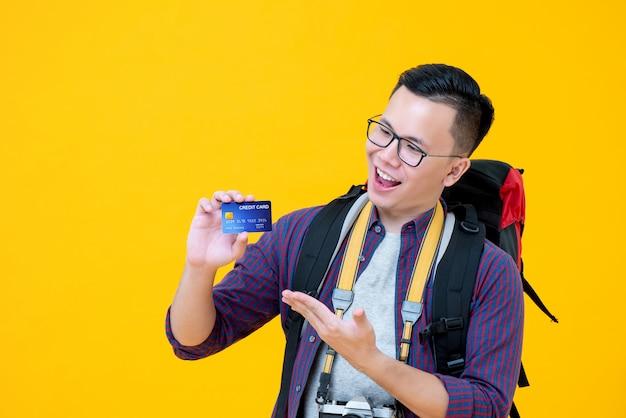 Mochileiro de turista asiático animado sorridente, mostrando o cartão de crédito na mão