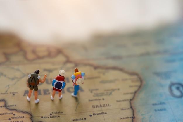 Mochileiro diminuto no mapa, conceito do curso em todo o mundo e a aventura.