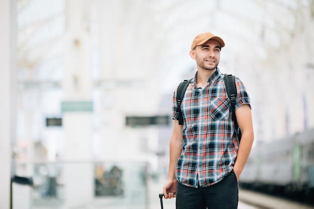 Mochileiro do tourist man e mala para viajar na estação de trem