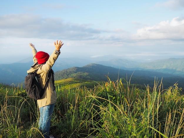 Mochileiro feliz mulher levantar os braços para o ar no topo da montanha