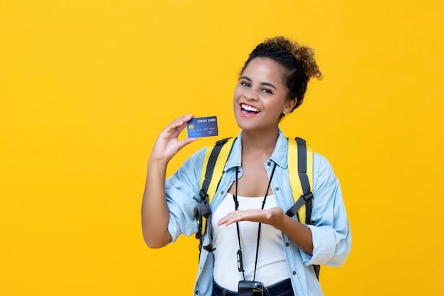 Mochileiro feminino americano africano feliz segurando o cartão de crédito