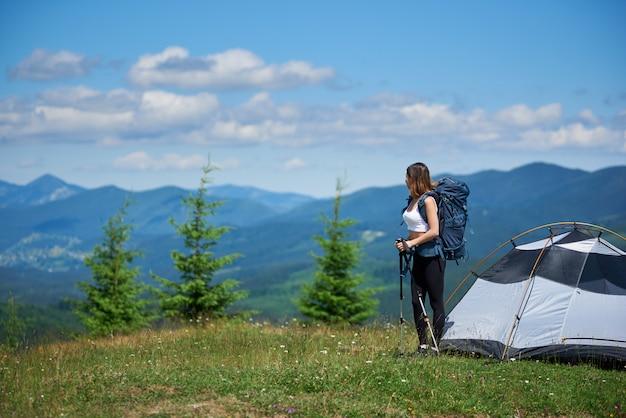 Mochileiro feminino desportivo com mochila e bastões de trekking perto da tenda, no topo de uma colina contra o céu azul e nuvens, olhando para longe, descansando depois de caminhadas, aproveitando a manhã ensolarada nas montanhas