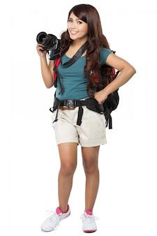 Mochileiro feminino saindo de férias com mochila e câmera