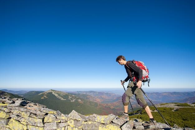 Mochileiro homem caminhando no cume rochoso da montanha