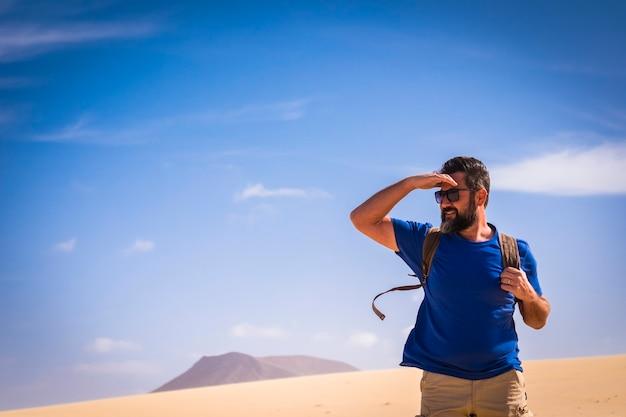 Mochileiro lifestlye pessoas com homem adulto caucasiano olhando lá fora viajando com uma mochila nas dunas do deserto com montanhas e céu azul claro na superfície