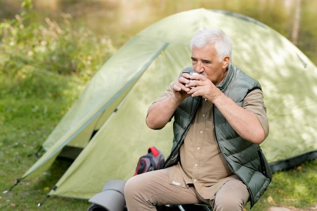 Mochileiro maduro com uma caneca de turista sentado perto da barraca, tomando uma bebida quente e descansando na floresta