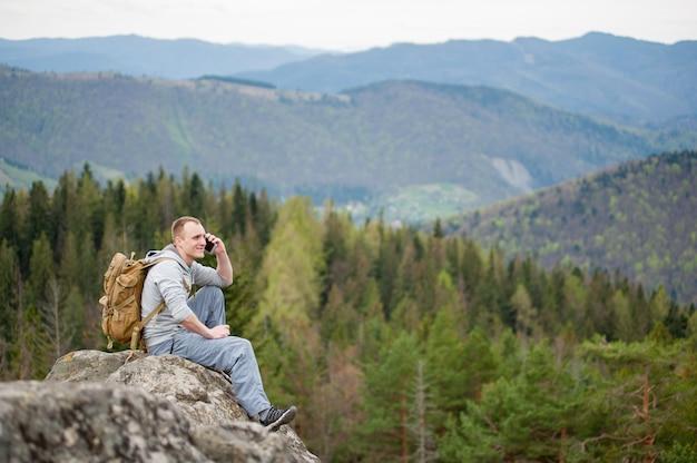 Mochileiro masculino sentado no pico da rocha
