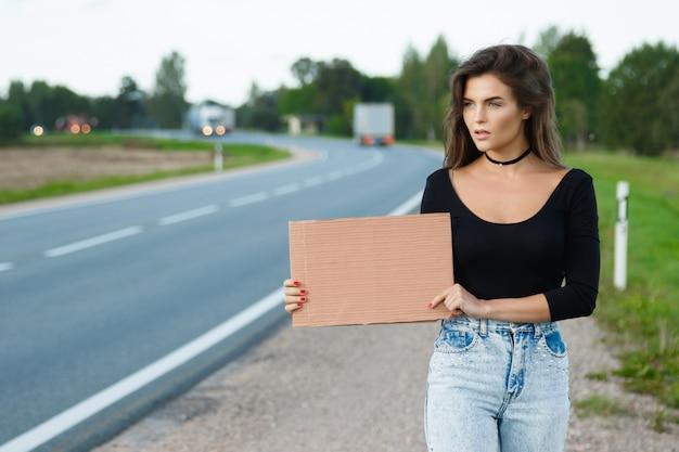 Mochileiro na estrada está segurando uma placa de papelão em branco