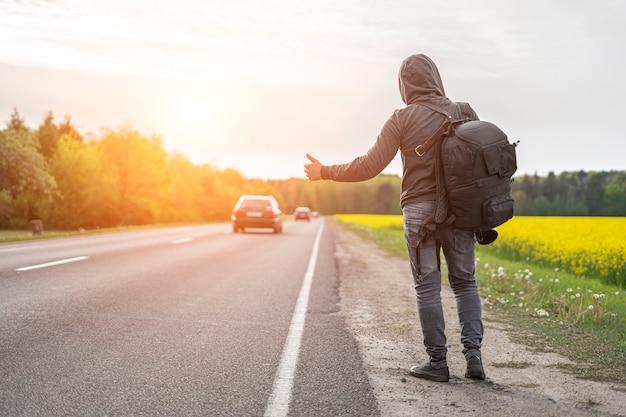 Mochileiro pega carro na estrada