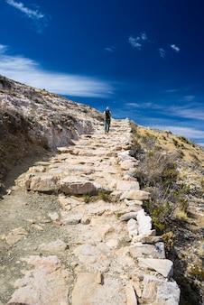 Mochileiro que explora as trilhas incas majestosas na ilha do sol, lago titicaca, entre o destino o mais cênico do curso em bolívia. viagens de aventura e férias nas américas.