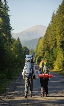 Mochileiros andando na estrada de montanha com mochilas