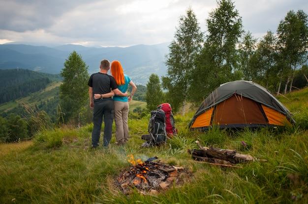 Mochileiros casal está de pé perto da fogueira e tenda ao pôr do sol