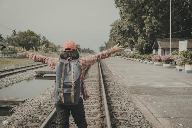 Mochileiros da moça que estão os braços acima nas trilhas do trem.