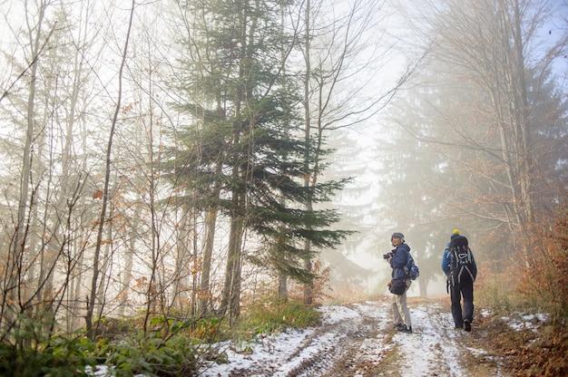 Mochileiros de homem e mulher caminhadas na trilha de montanha floresta nevoenta
