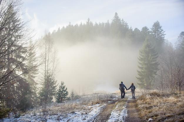 Mochileiros de homem e mulher desfrutando na trilha de montanha floresta nevoenta