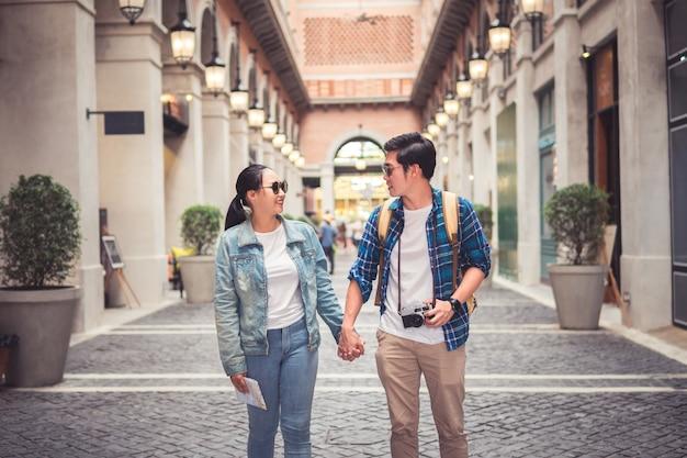 Mochileiros de turista casal asiáticos andando na rua enquanto viaja em férias com câmera e papel