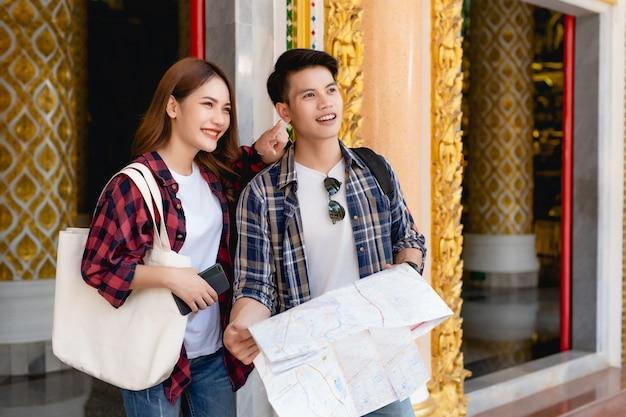Mochileiros de turistas de casal asiático sorridente em pé no lindo templo tailandês, uma linda mulher segurando um mapa de papel e um homem bonito fazendo check-in no smartphone com feliz nas férias