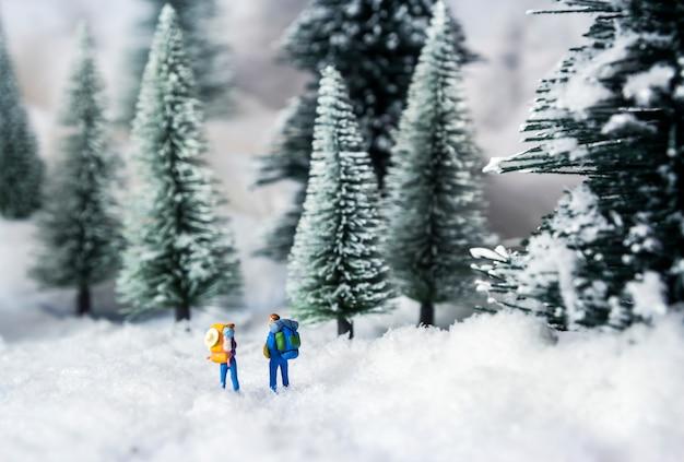 Mochileiros em miniatura andando na floresta de pinheiros durante o inverno
