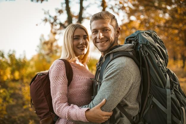 Mochileiros felizes no amor ri abraçando enquanto olha para a câmera e de pé contra o pano de fundo da natureza outono