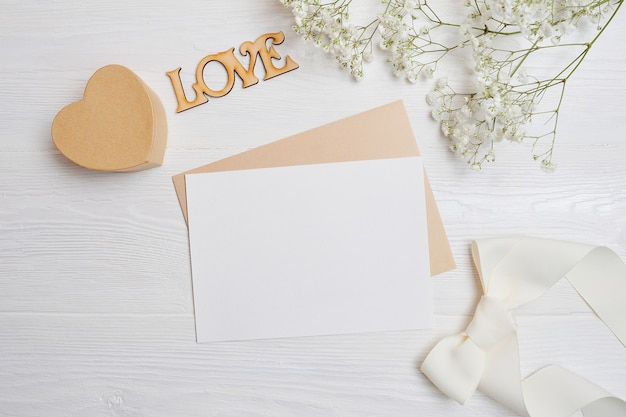 Mock-se carta com uma caixa de amor em forma de um coração encontra-se sobre uma mesa de madeira branca com flores de gipsófila.