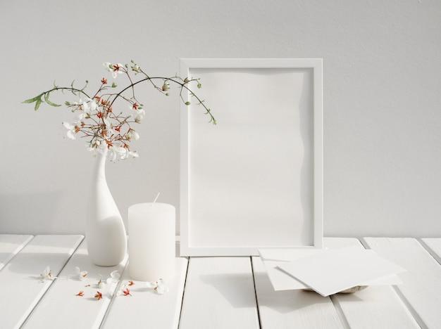 Mock-se cartão de convite branco, moldura de pôster, vela e belas flores clerodendron nodding em vaso erâmico na mesa de madeira interior de quarto branco, cartão em tom suave natureza morta
