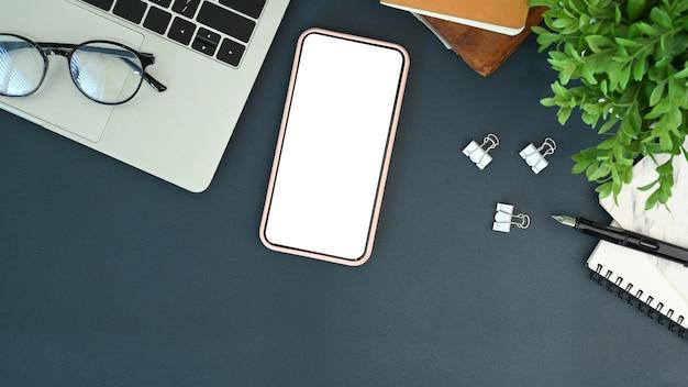 Mock-se celular com tela vazia e laptop na mesa do escritório.